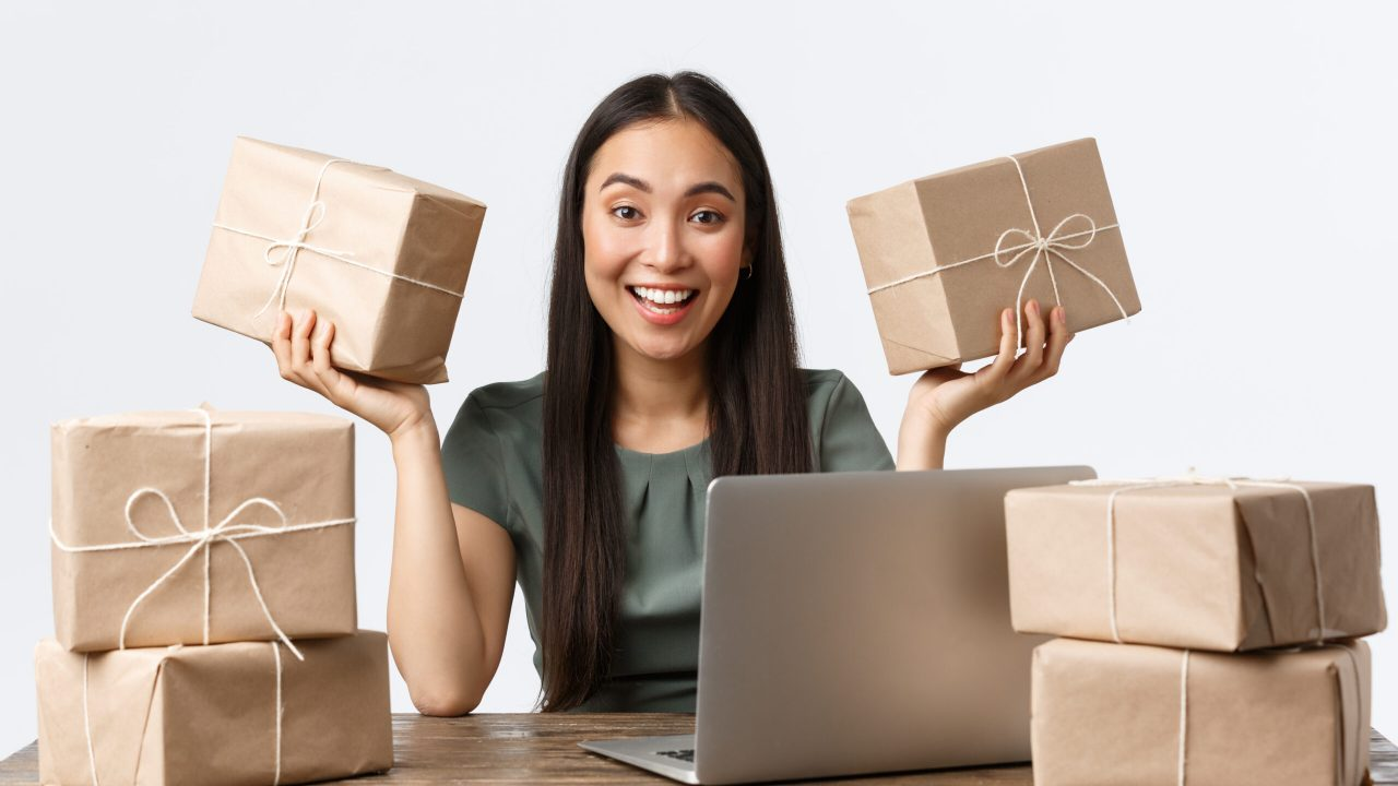 Small business owners, startup and e-commerce concept. Excited asian female entrepreneur sitting at desk with customer packages ready to delivery, smiling, answering client emails via laptop computer